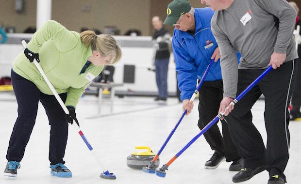 From left Kerry Busby, Bob McClay and Kent Busby sweep a rock during an Adult Learn to Curl session at the Calgary Curling Club on February 8, 2015. For curling package by Special Projects to run Feb. 19, 2015 with story by Jeff MacKinnon.  Noel West/For the Calgary Herald
